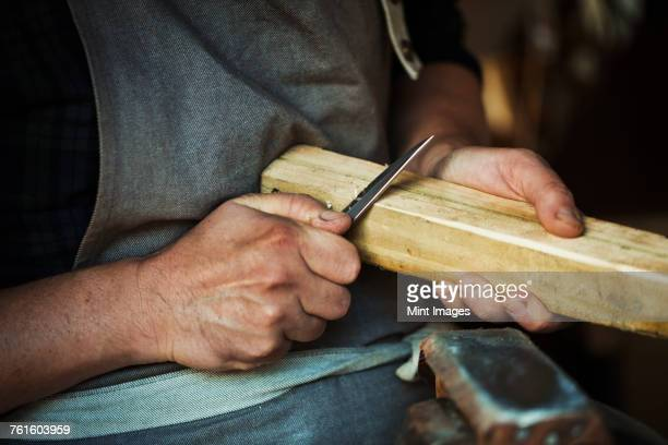 Close up of a craftsman cutting and paring the corners of a piece of wood with a sharp carving knife.