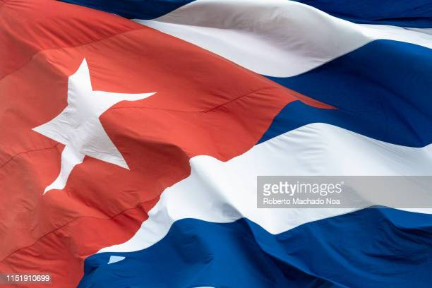 Close up of a Cuban flag waving in the wind The image shows the red triangle the star and part of the blue and white stripes