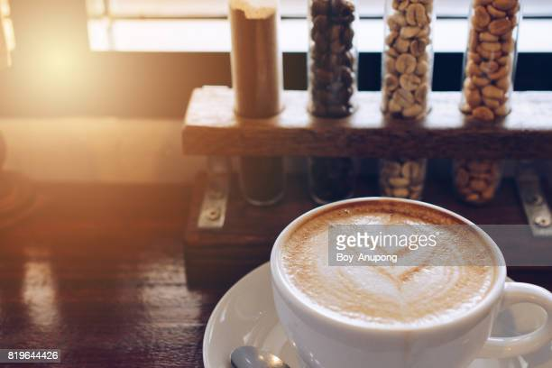 Close up of a cup of hot coffee latte on wooden table with a coffee beans in glass tube at the background.