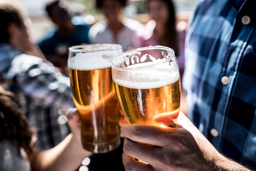Close up of a customers at a bar holding a beer and making a toast 915357028