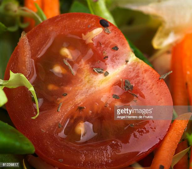 Close up of a cut cherry tomato in a salad.