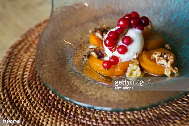 Close up of a dish of poached peaches with cream, walnuts and fresh red currants.