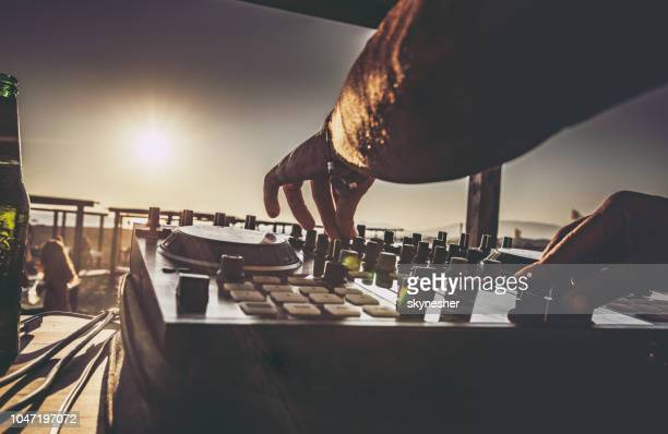 close up of a dj playing music on the beach at sunset. - dj stock pictures, royalty-free photos & images