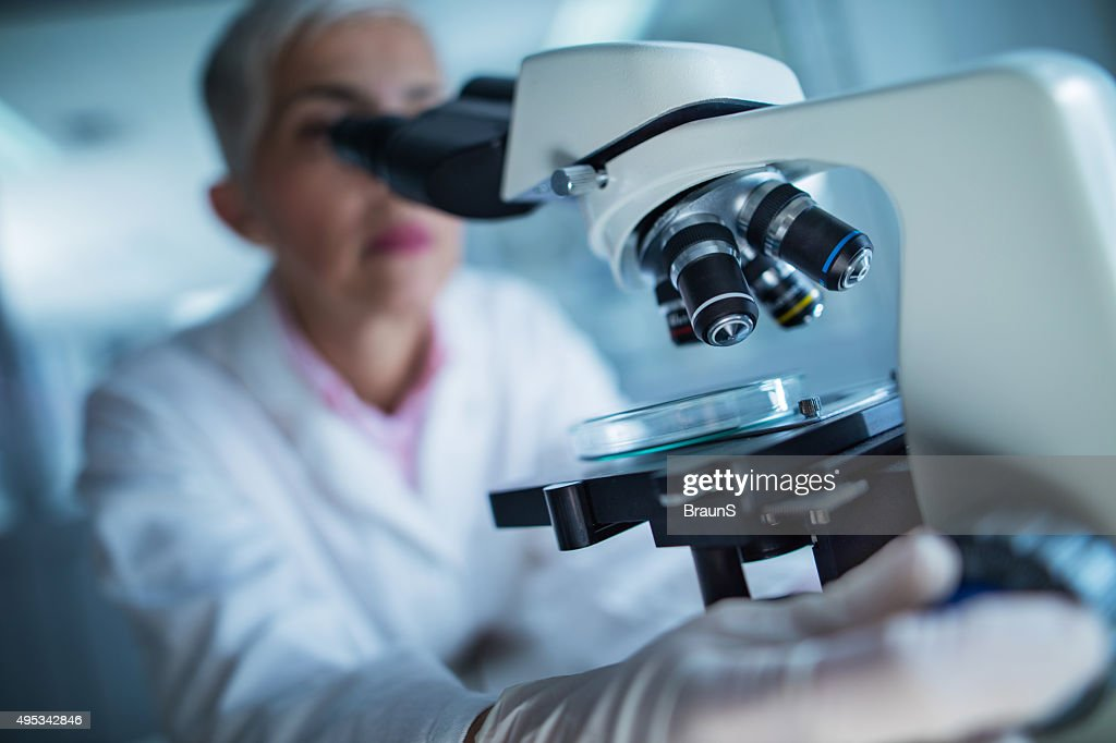 Close up of a doctor using microscope. : Stock Photo