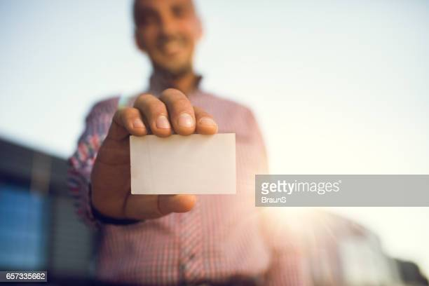 close up of a empty business card in man's hand. - business cards stock photos and pictures