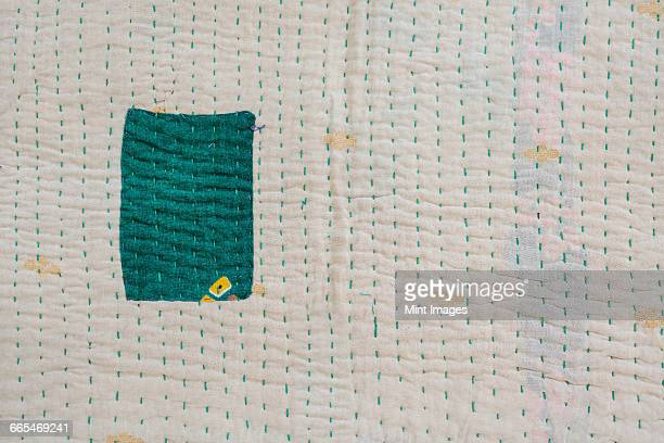 close up of a fabric bedspread or throw, with different fabrics sewn and quilted, a retro style and faded look. one green patch on a cream background. - キルト ストックフォトと画像