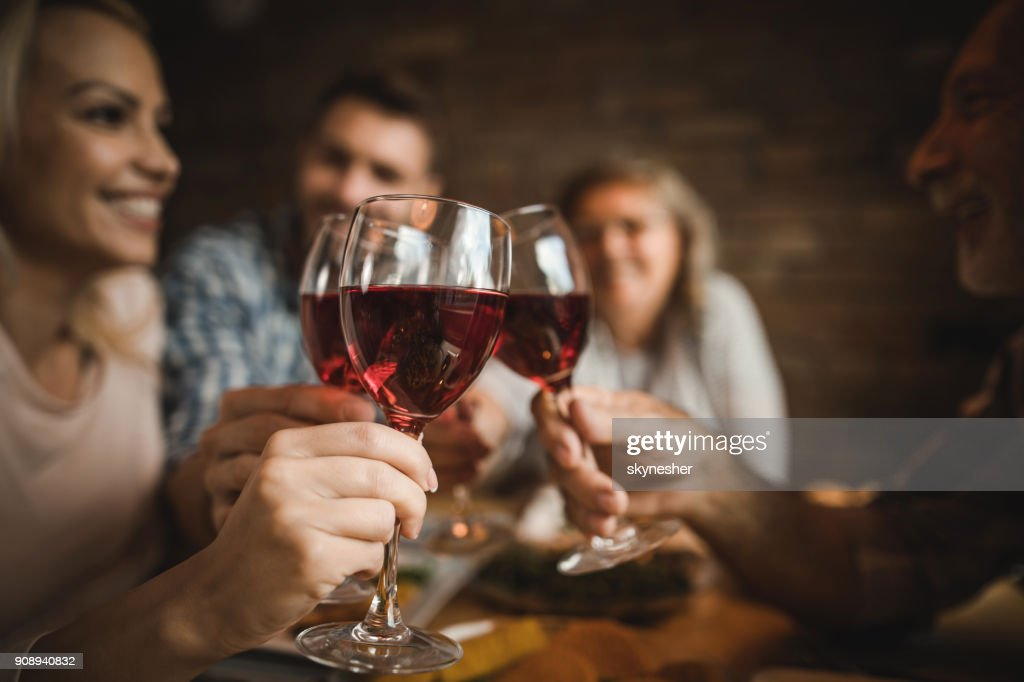 Close up of a family toasting with red wine at home. : Stock Photo
