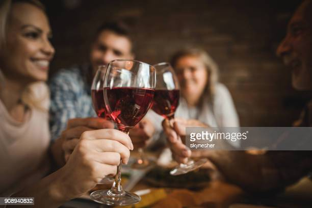 Close up of a family toasting with red wine at home.