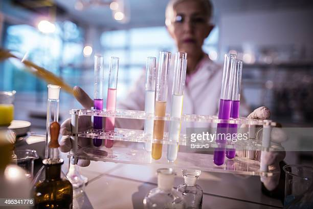 Close up of a female chemist holding test tubes.