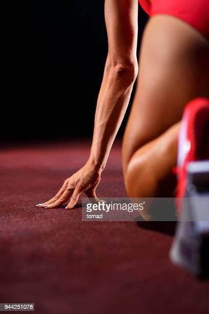 close up of a female sprinter in a starting block - arto umano foto e immagini stock