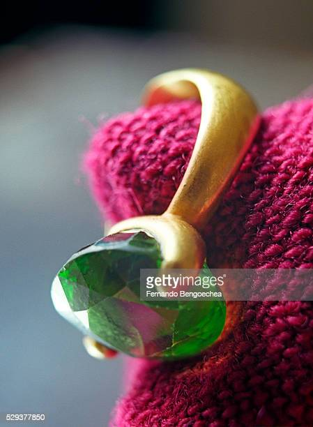 Close up of a finger ring bearing a green gemstone