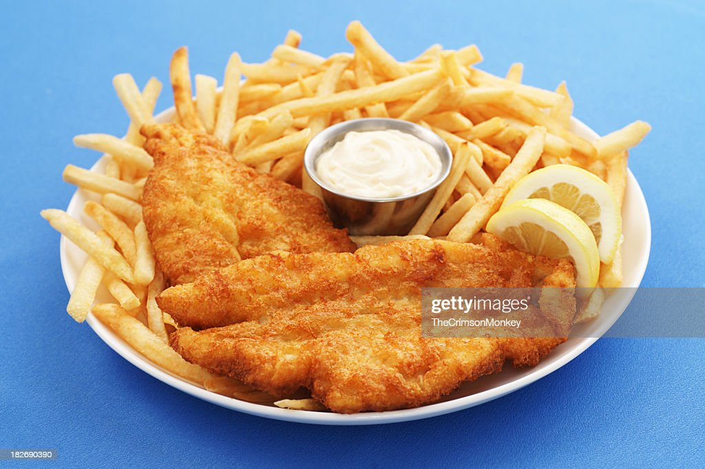 A close up of a fish and chips platter with dipping sauce : Stock Photo