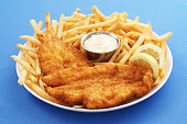 A close up of a fish and chips platter with dipping sauce