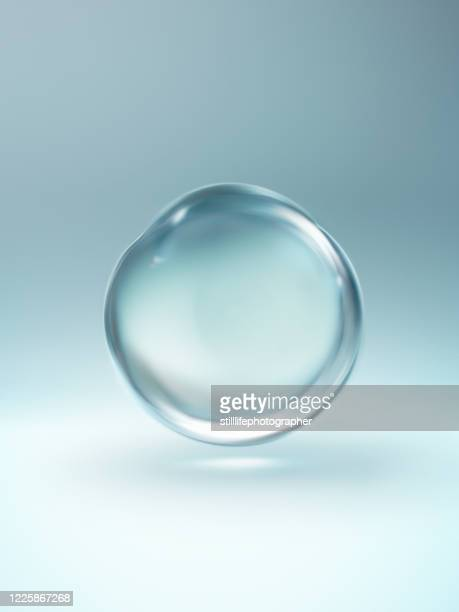 close up of a floating clear water droplet - wassertropfen stock-fotos und bilder