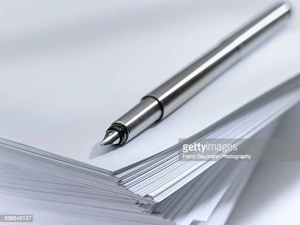 Close up of a fountain pen on a pile of papers