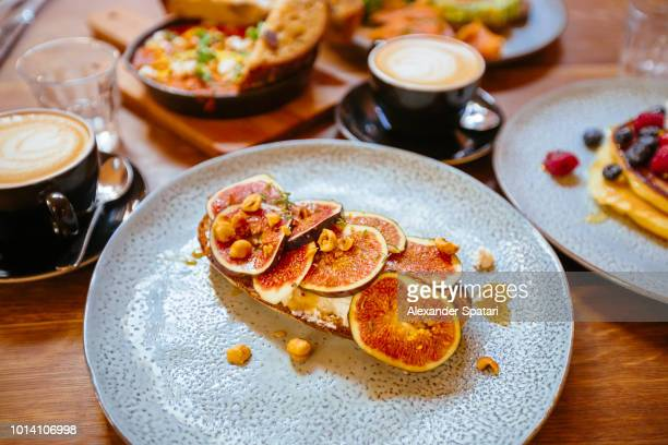Close up of a fresh fig sliced on a toasted bread on a plate