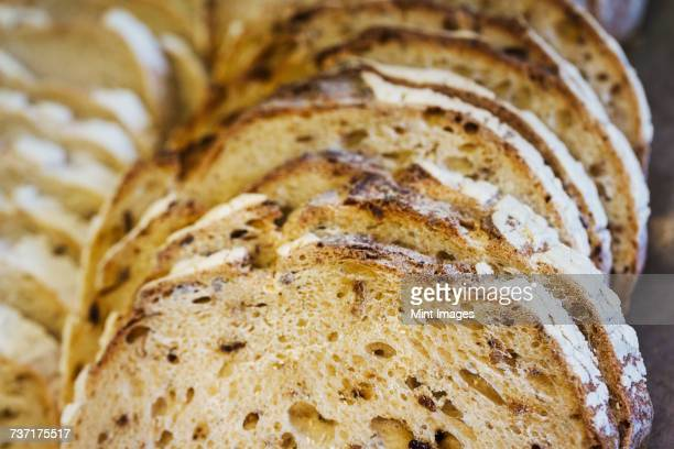 Close up of a freshly baked loaf of bread cut into slices.