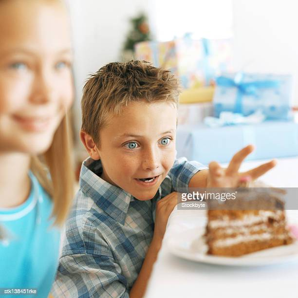 close up of a girl (12-13) and a boy (8-9) eating a slice of cake