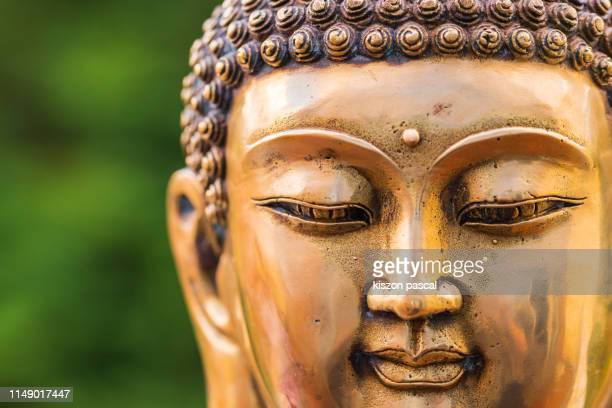 close up of a golden color buddha head statue . - religious symbol stock pictures, royalty-free photos & images