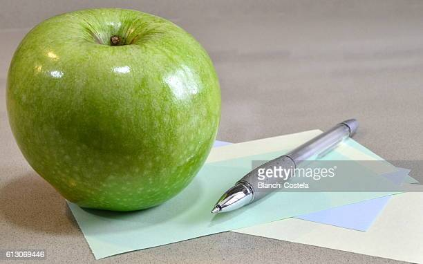 Close up of a green apple and pen