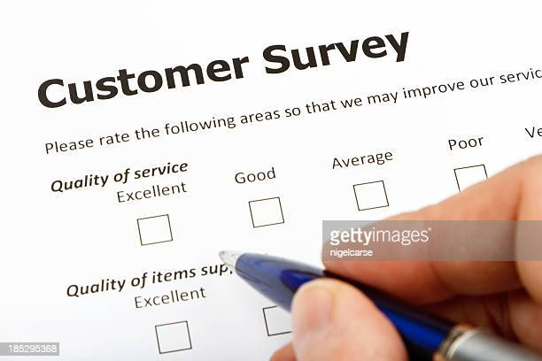Close up of a hand filling out a customer survey