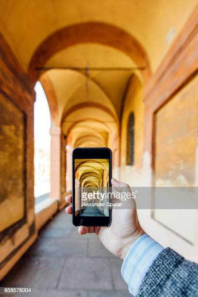 Close up of a hand holding smartphone taking picture of porticos in Bologna, Italy