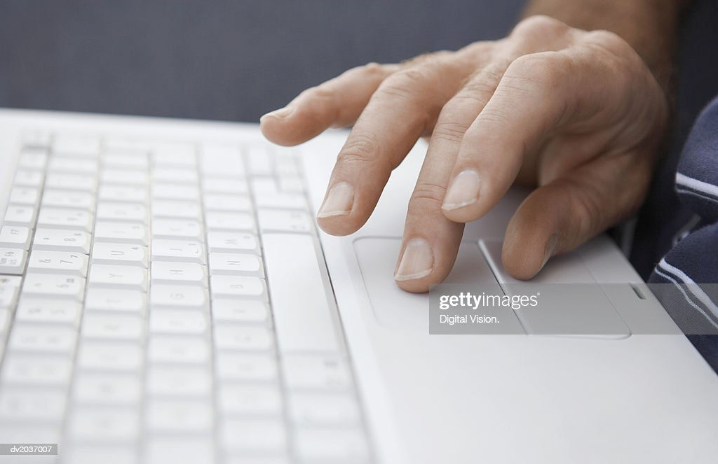 Close Up of a Hand Using a Laptop Computer : Stock Photo