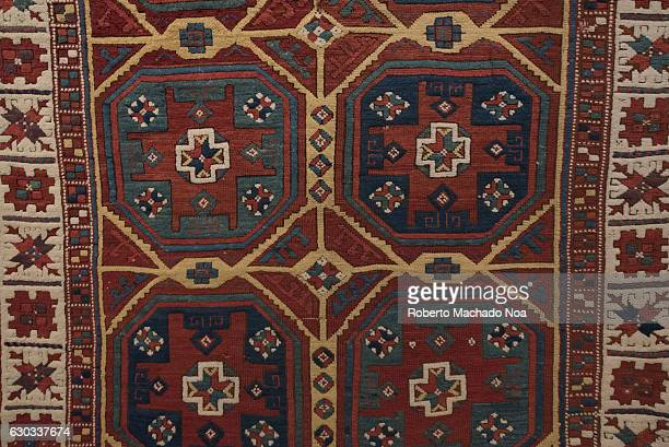 Close up of a hand woven maroon Persian carpet with geometric patterns