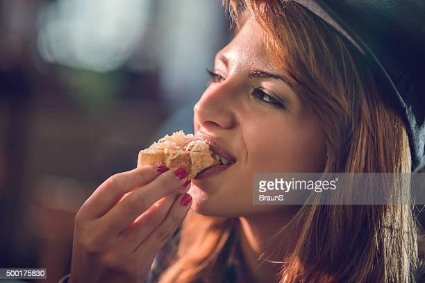 Close up of a happy woman biting a sandwich.