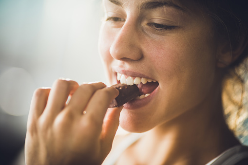 Close up of a happy woman eating chocolate. 938392194