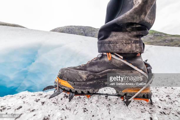 Close Up Of A Hiking Shoe On Ice Covered Rock Against Sky