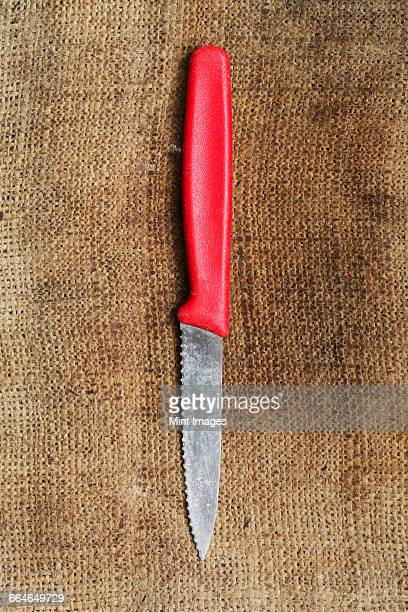 close up of a kitchen knife with a red plastic handle on burlap. - gekarteld stockfoto's en -beelden