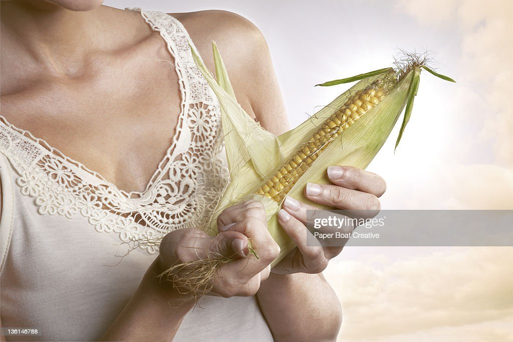 close up of a lady pulling open an ear of corn : Bildbanksbilder