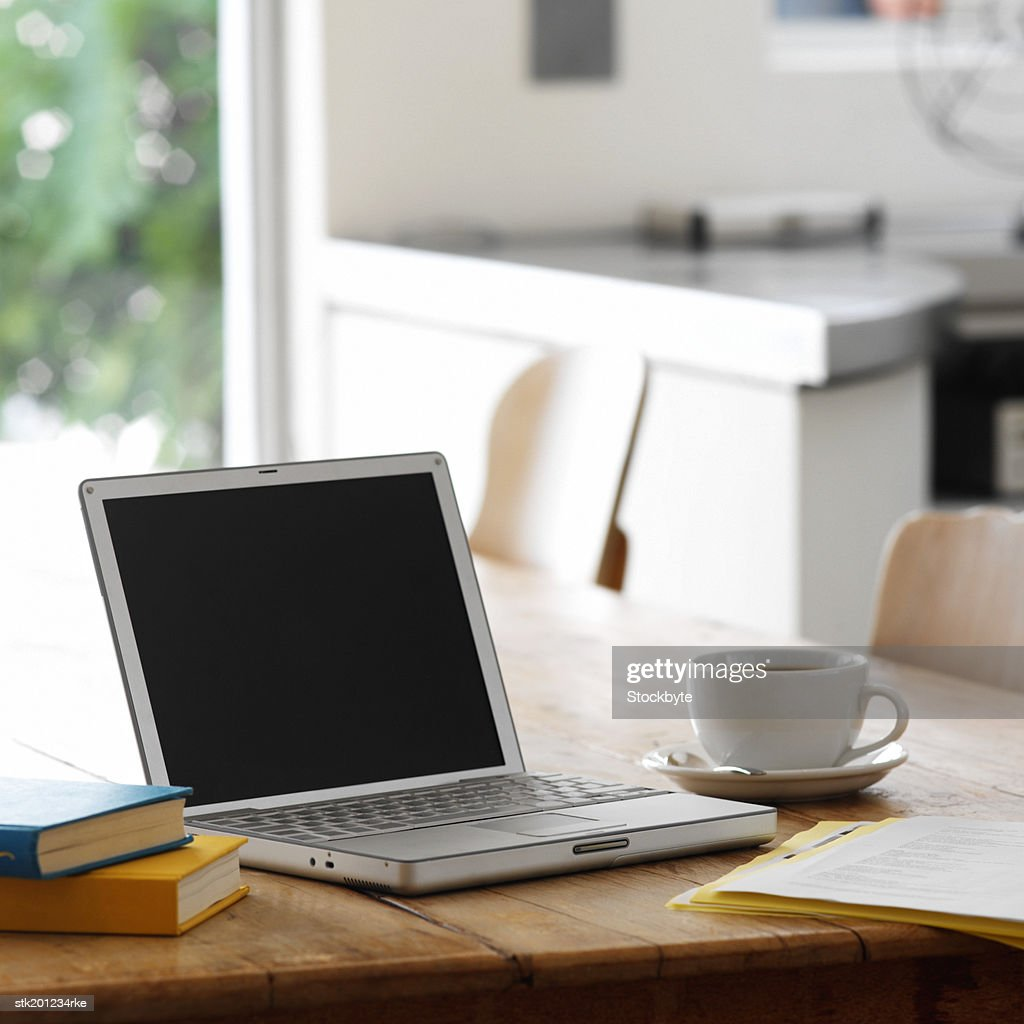 Close Up Of A Laptop On A Kitchen Table With A Cup Of Coffee Stock
