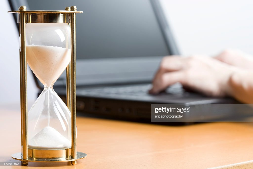 close up of a large egg timer and a person working on laptop stock
