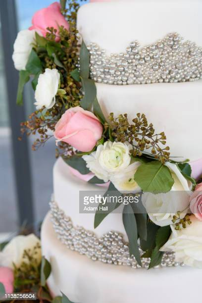 close up of a layered wedding cake with white and pink rose flowers, beads and leaves - utah wedding stock pictures, royalty-free photos & images