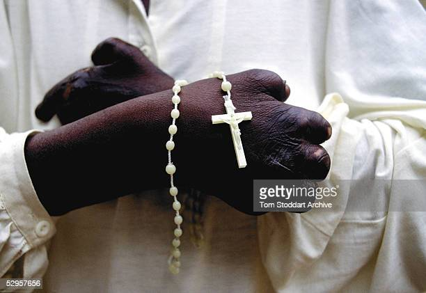 A close up of a leper's hands and cross at Mutemwa Leprosy settlement in Zimbabwe