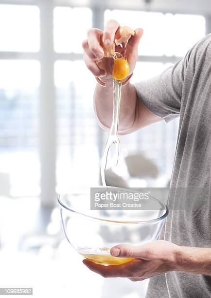 Close up of a man cracking an egg in to a bowl