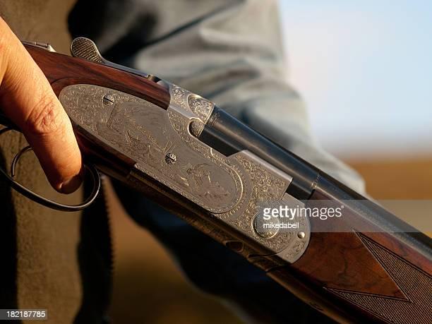 A close up of a man holding a shotgun