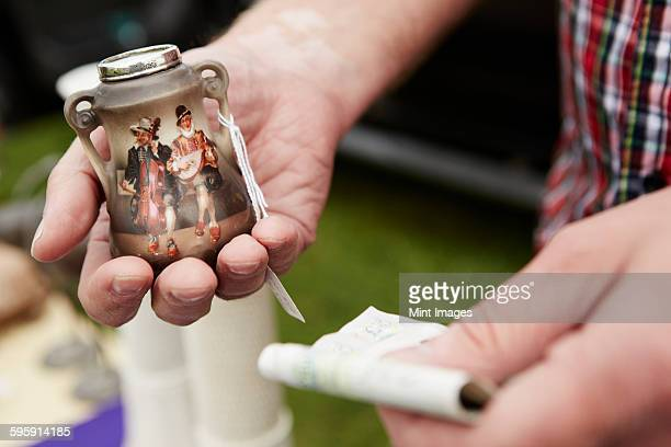 close up of a man holding a vintage pot and british currency, cash, at a flea market. - antique stock pictures, royalty-free photos & images