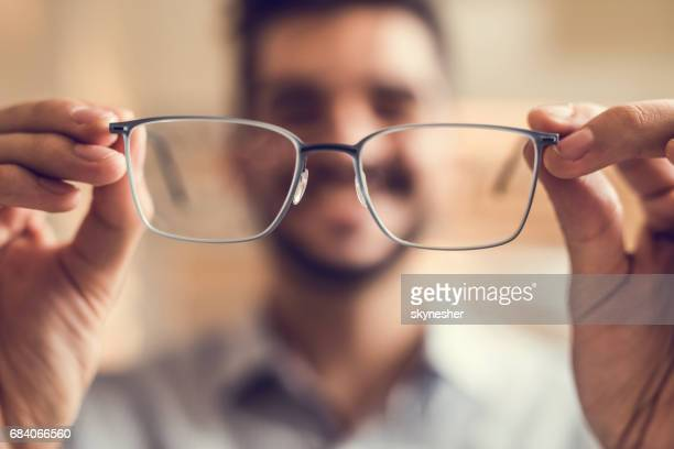 Close up of a man holding eyeglasses before trying them on.