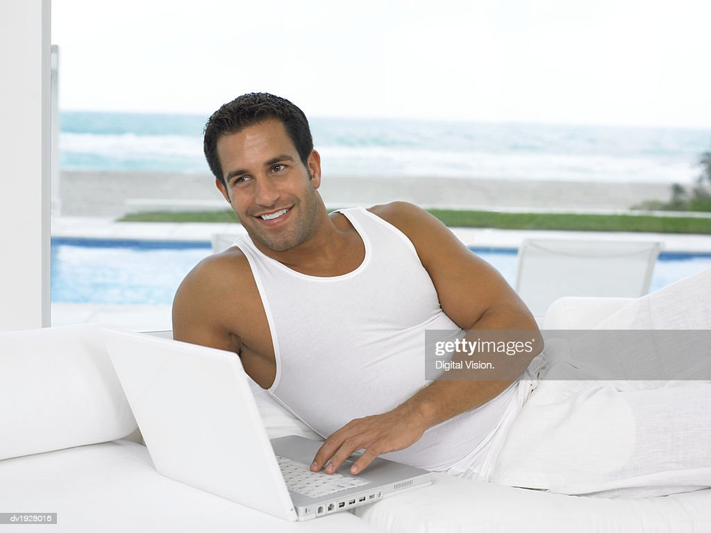 Close Up of a Man Lying on Sofa in His Pajamas Using His Laptop : Stock Photo