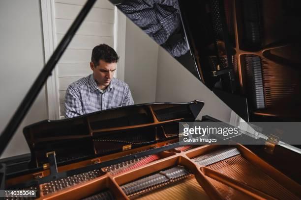 close up of a man playing baby grand piano - グランドピアノ ストックフォトと画像