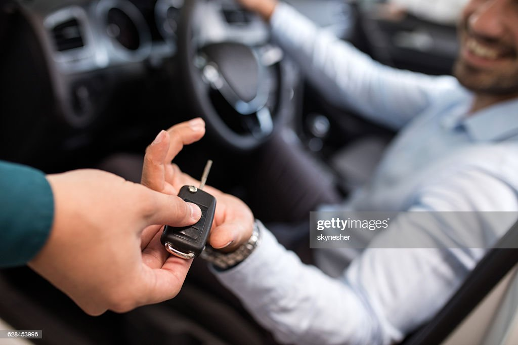 Close up of a man receiving new car key. : Stock Photo