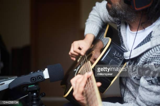 close up of a man recording on portable device at home - portable information device imagens e fotografias de stock