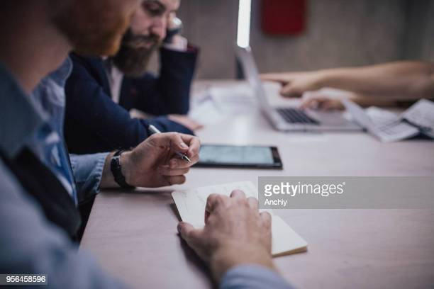 Close up of a man taking notes on a business meeting