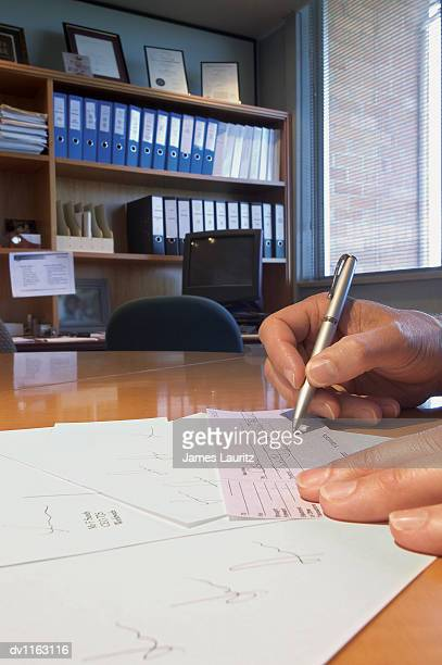 Close up of a Man Writing a Fraudulent Cheque