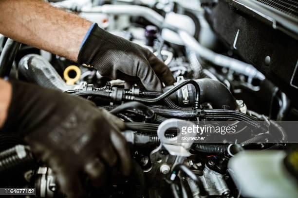 ワークショップで車のポンプを調べる整備士のクローズアップ。 - ディーゼル ストックフォトと画像