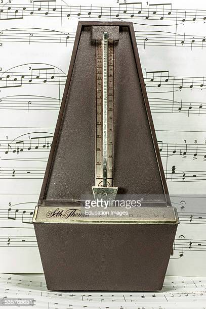Close up of a metronome against a background of sheet music This is a device that measures beats per minute in music