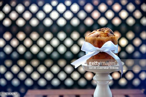 close up of a mini panettone with chocolate chips decorated with a white bow on a wooden table ready be to tasted - ribbed stock pictures, royalty-free photos & images